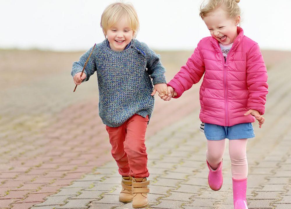 Happy kids having fun. Spring/summer/autumn outdoor active leisure for children. Portrait of little boy and girl playing on kindergarten back yard